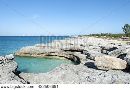 The Scenic View Of Grand Bahama Island Eroded Shore With Industrial Ships In A Background.