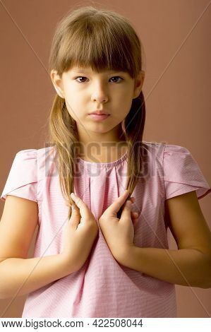 Portrait Of Lovely Girl With Ponytails. Front View Of Adorable Child In Pink Blouse Posing In Studio