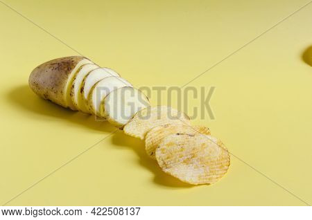 The Concept Of Turning Potatoes Into Chips. Potatoes And Potato Slices And Fluted Chips Close Up On