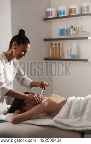 Smiling Masseur Doing Gua Sha Scrapping Tsm Treatment. Woman Relaxing During Gouache Massage, Lying