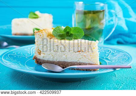 Sliced Cheesecake. Delicious Sweet Cheesecake With Mint Tea On Blue Background