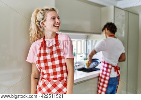 Young caucasian woman wearing apron and husband doing housework washing dishes looking away to side with smile on face, natural expression. laughing confident.