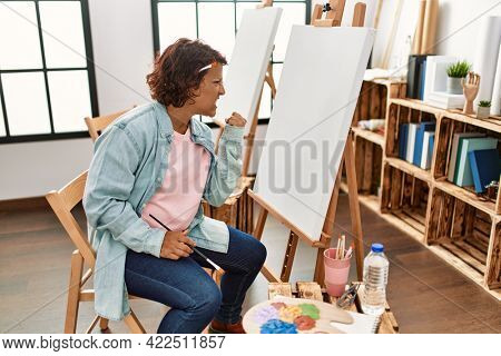 Middle age hispanic woman at art studio painting on canvas annoyed and frustrated shouting with anger, yelling crazy with anger and hand raised