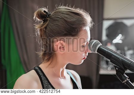 Young Woman Standing Next To A Microphone In A Studio. Vocal Audio Song Recording. Performance Rehea