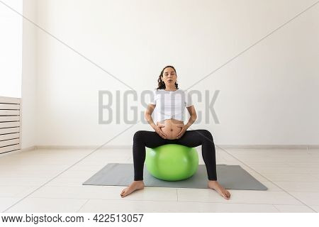 A Young Pregnant Woman Doing Relaxation Exercise Using A Fitness Ball While Sitting On A Mat. Copysp