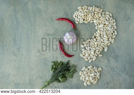 White Beans With Spices On A Green Wooden Background. White Beans Shaped Like A Question Mark With C