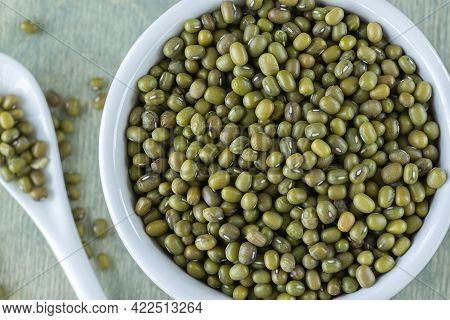 Mung On A Green Wooden Background. Beans Of Mung Shaped Like A Question Mark With Copy Space. Food C