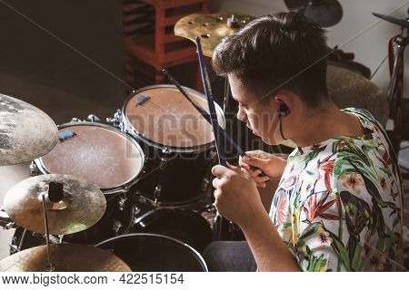 Teenager Boy Drummer Playing On Rehearsal In A Studio. Rock Musician Male Teen Performing A Song. Re