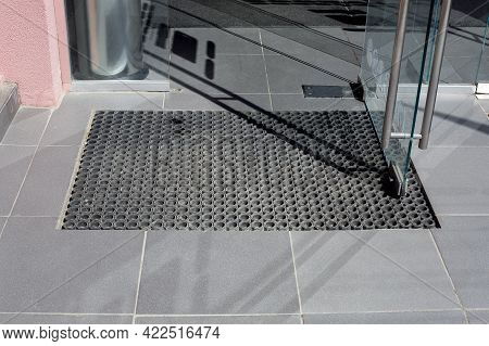 Threshold Made Of Gray Ceramic Tiles At Entrance To Store With A Rubber Foot Mat And Open Glass Door