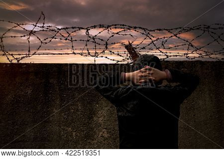 Criminal. Prison. A Man At The Prison Wall With Barbed Wire At Sunset. Crime And Lawlessness.