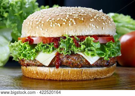 Delicious Burger With Sauce. Hamburger. Delicious Grilled Burger With Cheese, Salad And Tomatoes On