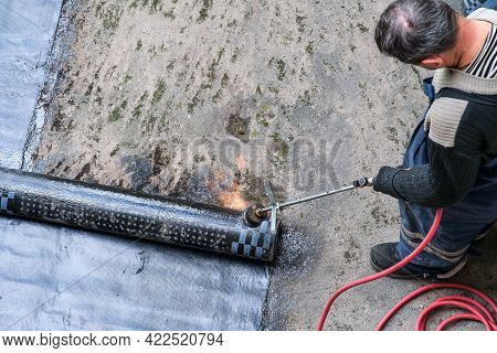 A Worker Installing Resin Foil On The Roof Of A Building. Waterproof System With Gas And Fire Torch.