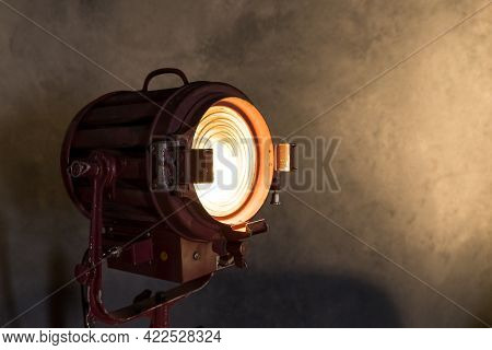 Old Movie Projector With A Lens And A Hot Lamp.vintage Lamp Projector Near The Grey Wall. Room In Lo