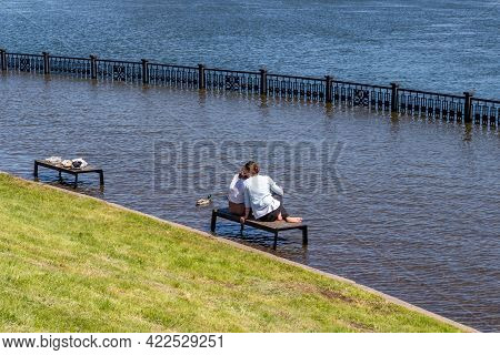 Krasnoyarsk, Russia - June 1, 2021: Young Women Sit On Benches On A Flooded City Embankment. Floodin