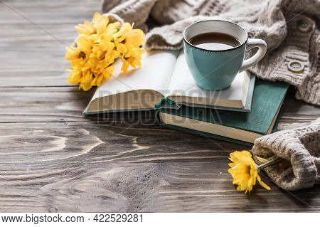 Spring Morning Coffee. A Cup Of Coffee On An Open Book On A Wooden Table And A Warm Sweater Against