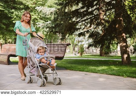 young mother walks with her little son in the park, pushes the stroller.