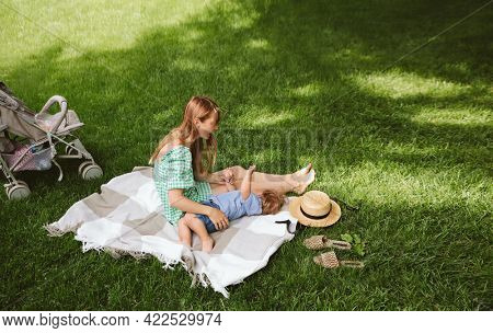 Young mother and little son are resting in the park sitting on a blanket. Copy space
