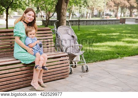 Young mother walks with her little son in the summer in the park, sits on a bench.
