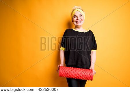 A Cute Smiling Elderly Woman In A Black T-shirt And With A Sports Bandage On Her Head Holds A Fascia