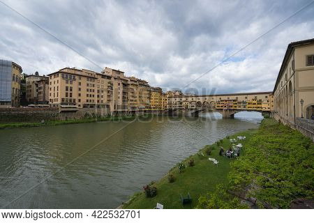 Florence, Italy - May 07, 2021, People Resting On A Green Lawn Near The Arno River On Background Of