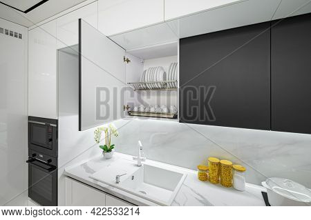 Luxury large modern white and black kitchen interior used as showcase, dish dryer is open showing furniture inside