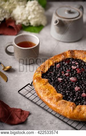 Homemade Blueberry Galette, Tart On The Table With Tea And Flowers.