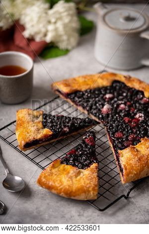 Sliced Homemade Blueberry Galette, Tart On The Table With Tea And Flowers.