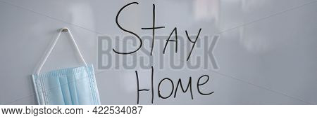 Lettering On White Board Stay At Home Next To Protective Medical Mask