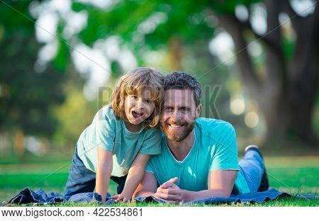 Childhood And Parenthood Kids Concept. Happy Father And Son Playing Together Outdoor.