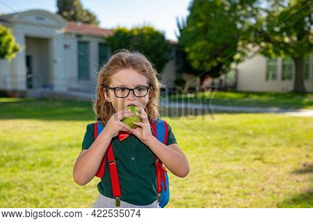 Child With Rucksacks In The School Park. Pupils With Backpacks Outdoors. Schoolboy Eating Apple.
