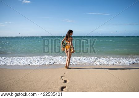 Playful Slim Woman In Sexy Bikini Stands Back Walks Away Hawaii Or Maldives Sea Beach Holding Fresh