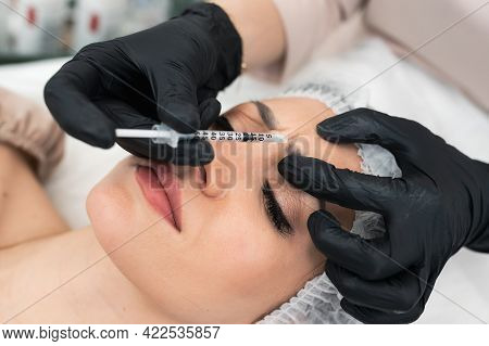 Cosmetologist Doctor Gives A Injection In The Eyebrow Or Forehead. Young Woman Gets Beauty Facial In