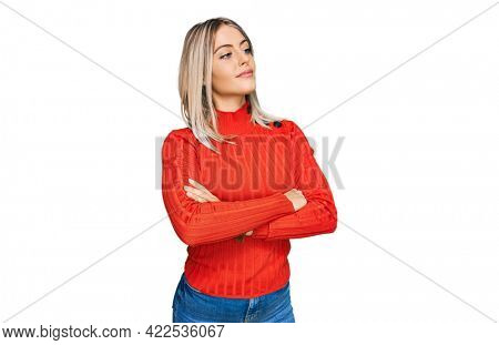 Beautiful blonde woman wearing casual clothes looking to the side with arms crossed convinced and confident
