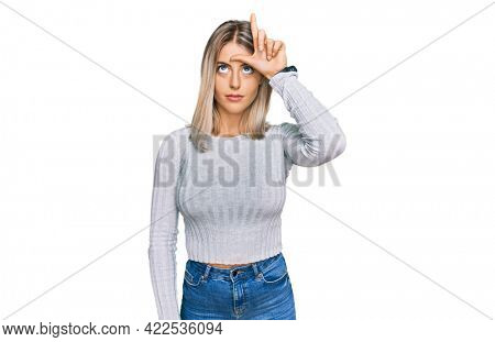 Beautiful blonde woman wearing casual clothes making fun of people with fingers on forehead doing loser gesture mocking and insulting.