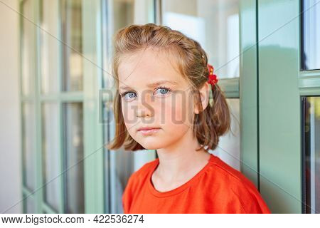 The Girl Looks At The Camera With A Serious Expression On Her Face.