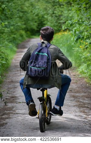 A Teenager About 14 Years Old Rides A Children's Bicycle Along A Forest Path With A Backpack, Legs W