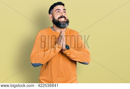 Hispanic man with beard wearing casual winter sweater begging and praying with hands together with hope expression on face very emotional and worried. begging.