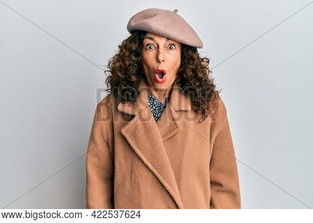 Middle age hispanic woman wearing french look with beret afraid and shocked with surprise expression, fear and excited face.