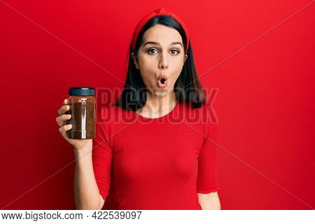 Young hispanic woman holding soluble coffee scared and amazed with open mouth for surprise, disbelief face