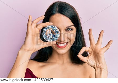 Young hispanic woman holding brilliant diamond stone on eye doing ok sign with fingers, smiling friendly gesturing excellent symbol