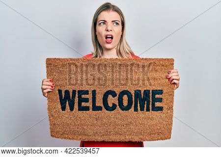 Beautiful caucasian woman holding welcome doormat angry and mad screaming frustrated and furious, shouting with anger. rage and aggressive concept.
