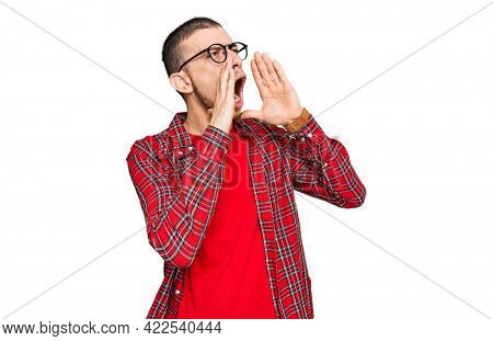 Hispanic young man wearing casual clothes shouting angry out loud with hands over mouth