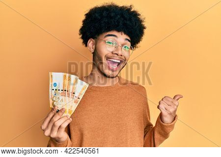 Young african american man with afro hair holding 500 philippine peso banknotes pointing thumb up to the side smiling happy with open mouth