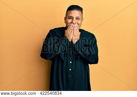 Young latin priest man standing over yellow background laughing and embarrassed giggle covering mouth with hands, gossip and scandal concept