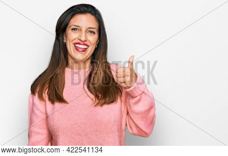 Beautiful hispanic woman wearing casual winter sweater smiling happy and positive, thumb up doing excellent and approval sign