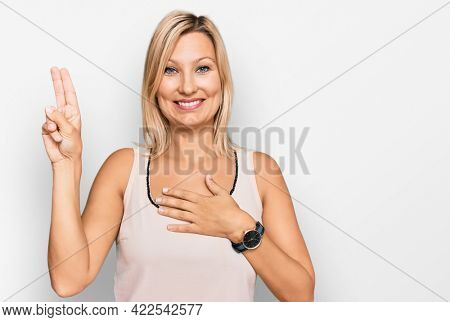 Middle age caucasian woman wearing casual clothes smiling swearing with hand on chest and fingers up, making a loyalty promise oath