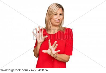 Middle age caucasian woman wearing casual clothes disgusted expression, displeased and fearful doing disgust face because aversion reaction. with hands raised