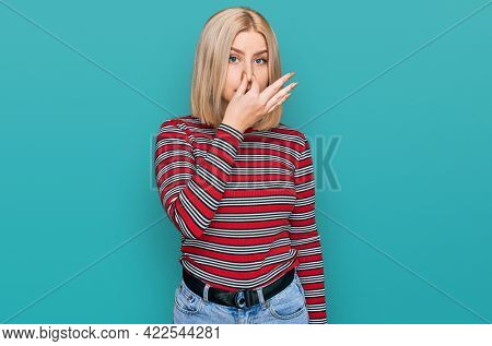 Young blonde woman wearing casual clothes smelling something stinky and disgusting, intolerable smell, holding breath with fingers on nose. bad smell