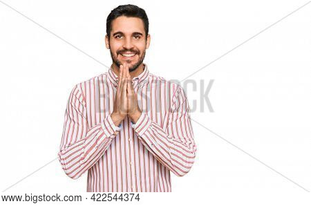 Young hispanic man wearing business shirt praying with hands together asking for forgiveness smiling confident.