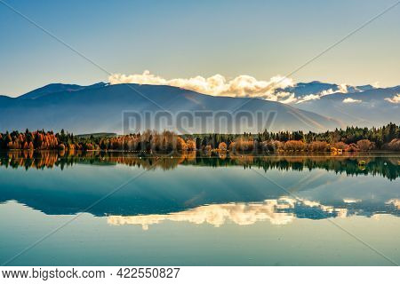 The Snow Capped Southern Alps Mountain Range Reflected On The Calm Water At Sunsrise
